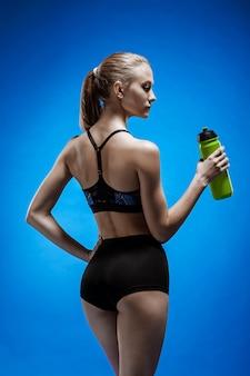 Atleta muscolare della giovane donna con un'acqua sul blu