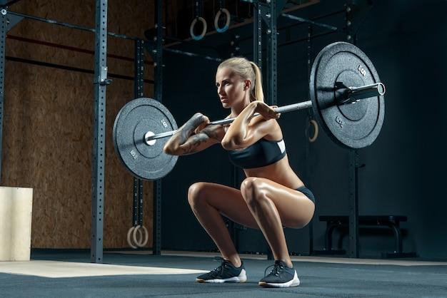 체육관에서 바벨과 함께 스쿼트를 하 고 근육 질의 젊은 여자 여성 보디 운동을 하 고