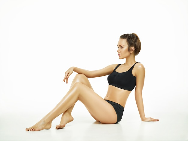 Muscular young woman or female athlete posing at studio isolated on white