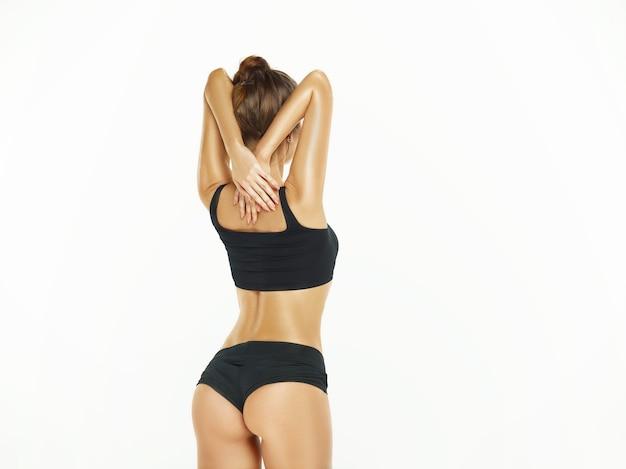 흰색 배경에 격리된 스튜디오에서 포즈를 취하는 근육질의 젊은 여성 또는 여성 운동선수. 완벽한 몸매에 맞는 백인 모델. 피트니스, 스포츠, 아름다움, 신선한 피부 개념.
