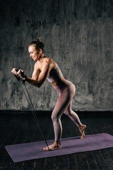 Мускулистая молодая женщина с красивым телом в спортивной одежде тренируется с резиновой лентой сопротивления