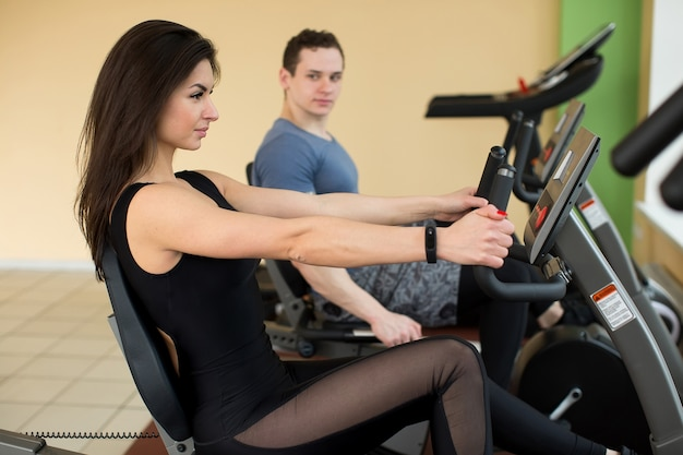 Muscular young woman working out on the exercise bike at the gym intense cardio workout