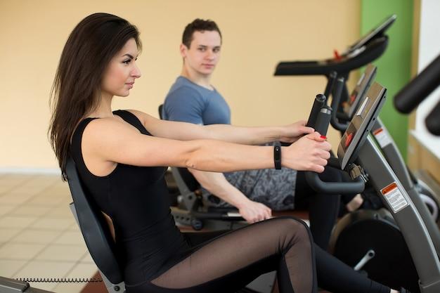Мускулистая молодая женщина, тренирующаяся на велотренажере в тренажерном зале, интенсивная кардио-тренировка