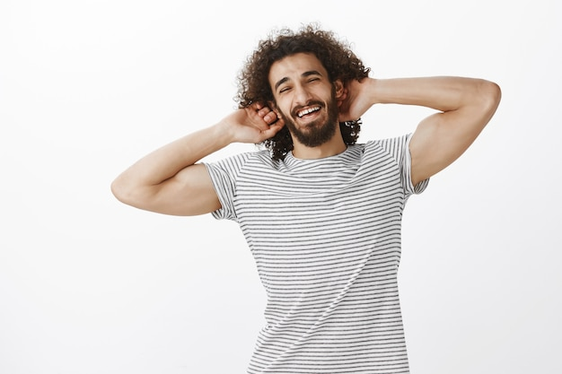 Musculine confident hispanic guy with joyful attitude and curly hair, holding hands behind head and smiling with carefree expression