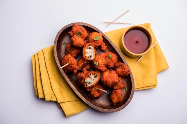 Гриб 65, рецепт закуски или закуски из индии. подается в тарелке с кетчупом. выборочный фокус