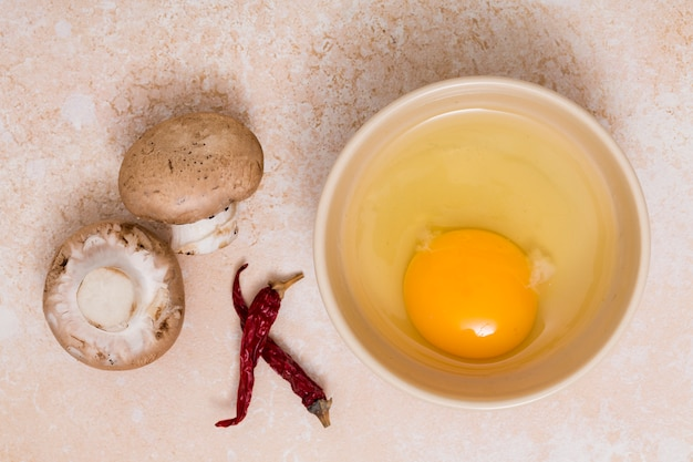Mushroom; chili pepper and egg yolk bowl on textured backdrop