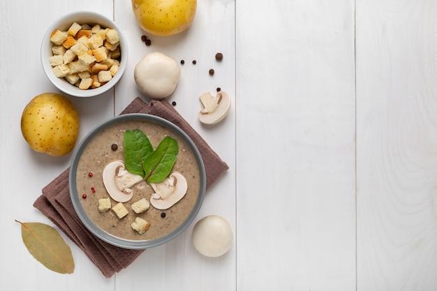 白い木の板にキノコのクリームスープ。上面図