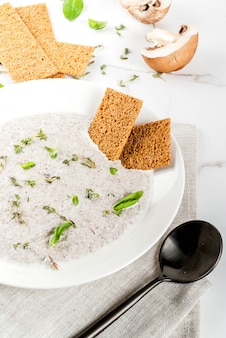 Mushroom cream soup with brown fried champignons and herbs