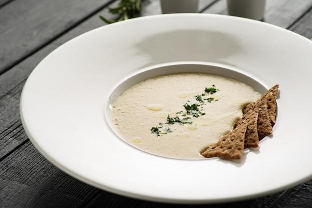 하얀 접시에 크래커와 버섯 크림 스프. 식당 메뉴에 대한 개념