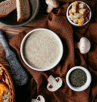 Грибной крем-суп с крекерами сверху на столе