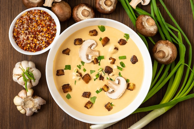 Mushroom cream soup on a wooden table with onions and croutons.