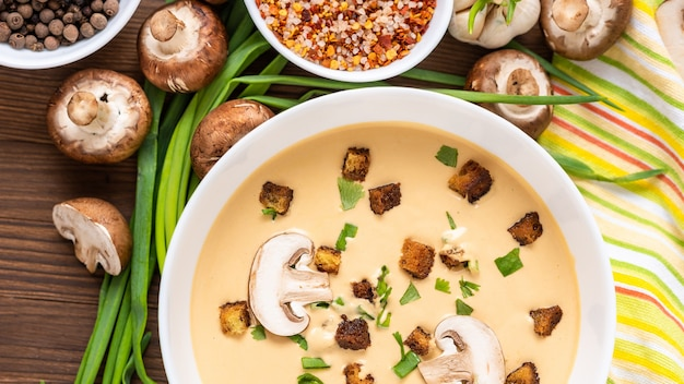 Mushroom cream soup on a wooden table with sliced mushrooms and onions.
