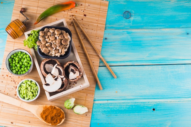 Mushroom; green peas; brussels sprouts; and spice on placemat over the wooden background