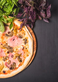 Mushroom and meat pizza on wooden board with leafy vegetables