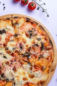Mushroom pizza on desk with tomatoes