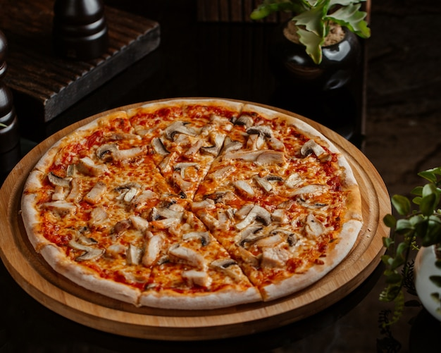 Mushroom pizza with tomato sauce and served in a round bamboo board