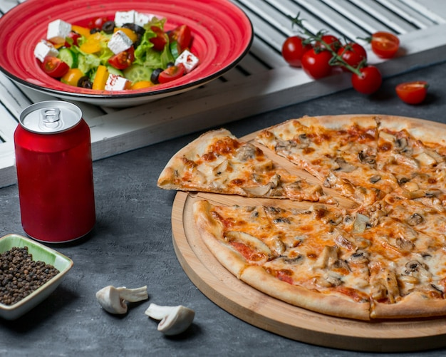 Mushroom pizza with vegetable salad and cola can