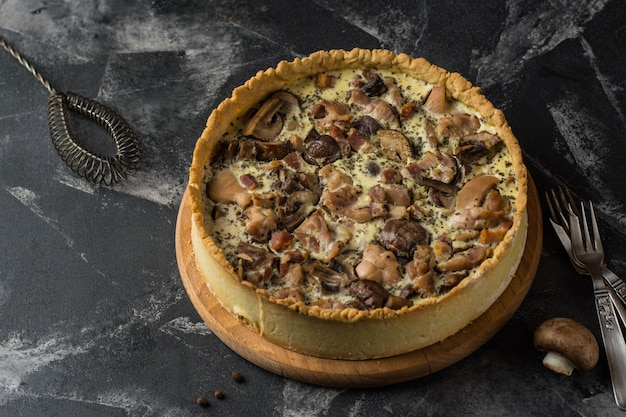 Mushroom quiche pie with champignons and cheese on dark background