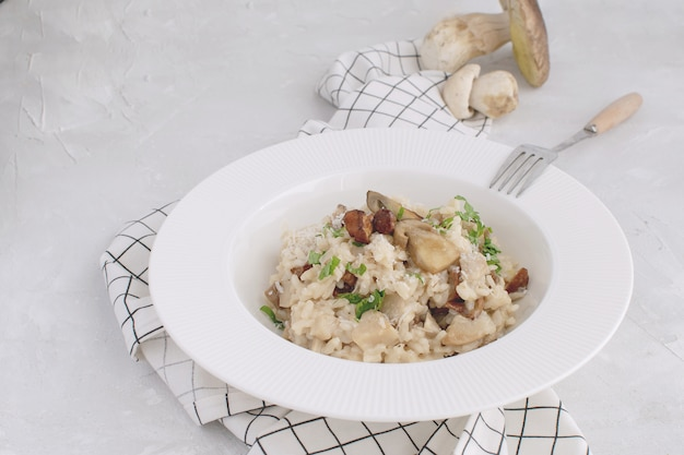 Mushroom risotto dish white background checkered napkin copy space