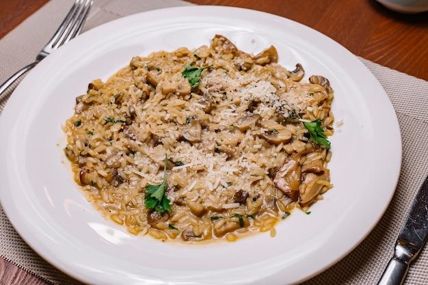 Risotto ai funghi guarnito con parmigiano grattugiato e prezzemolo