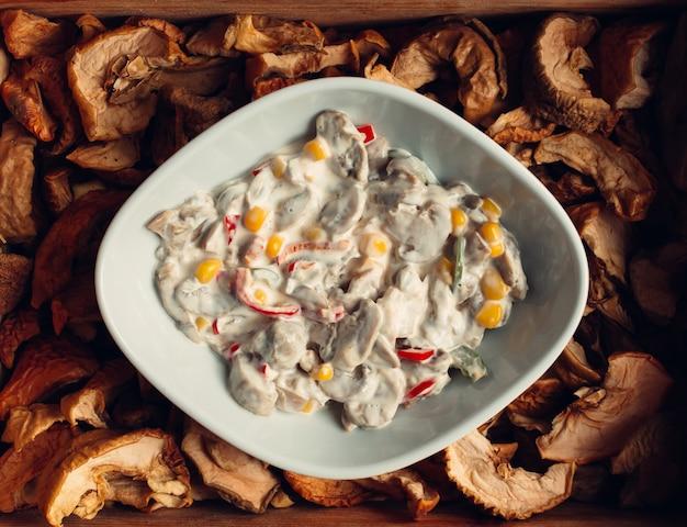 Mushroom salad with corn seeds and white cream sauce.