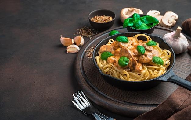 Грибной соус и паста с базиликом на темно-коричневом столе. вид сбоку с копией пространства.