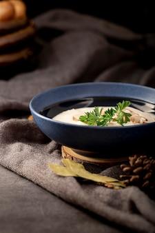 灰色の布の上の青い瓶にキノコのスープ