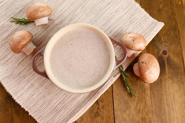木のテーブルの上に鍋にキノコのスープ