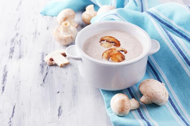 白い鍋にキノコのスープ、木製のテーブルのナプキンに