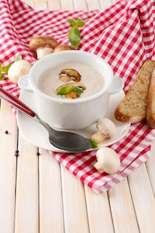白い鍋にキノコのスープ、ナプキン、木製のテーブルの上