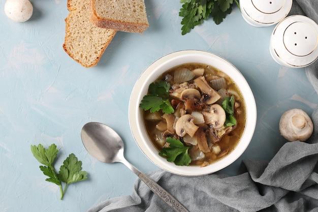 水色の背景に白いプレートのシャンピニオンとレンズ豆のキノコのスープ、上からの眺め