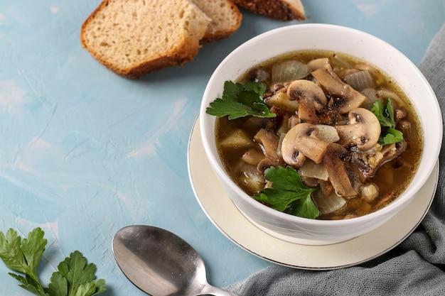 水色の表面の白いプレートにシャンピニオンとレンズ豆のキノコのスープ、上面図、コピースペース