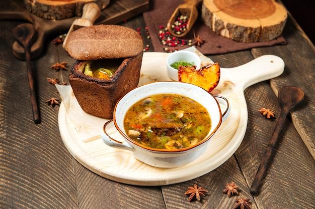 Грибной суп на деревянной доске с хлебом