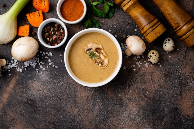 Mushroom soup puree in a plate with spices and kitchen requisites on a black table