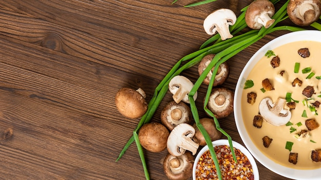 Mushroom soup with croutons, onions and spices. on a wooden table. top view. copy space.