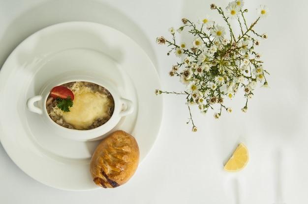Грибной суп с дольками лимона на белой поверхности с тенью фужеров
