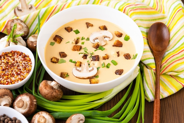 Mushroom soup with onions, garlic and pepper on a wooden table.