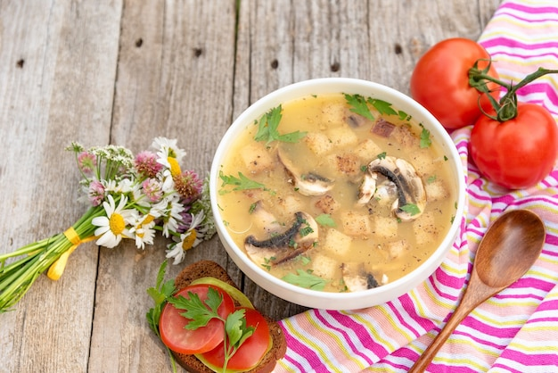 Mushroom soup with tomatoes on a wooden background.