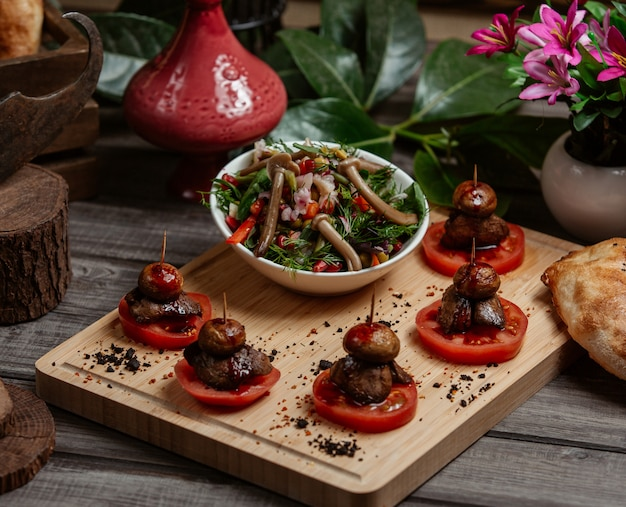 Mushroom vegetable salad in olive oil on a wooden board
