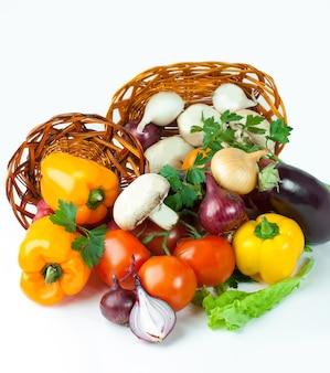 きのこと籐のかごの中のさまざまな新鮮な野菜。白い背景で隔離。コピースペース付きの写真