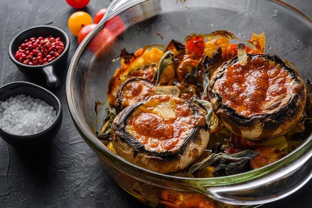Грибы, запеченные и фаршированные ингредиентами сыр чеддер, помидоры черри и шалфей в стеклянном горшке на черном каменном фоне, вид сбоку, выборочный фокус.