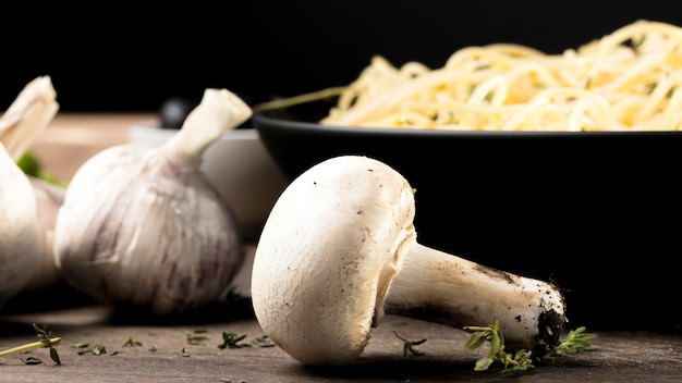 Грибы рядом с тарелкой со спагетти