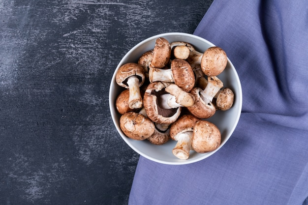 Mushrooms in a bowl on purple cloth on a dark table
