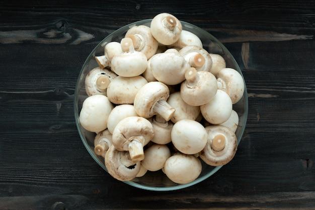 Mushrooms champignon on dark wood desk