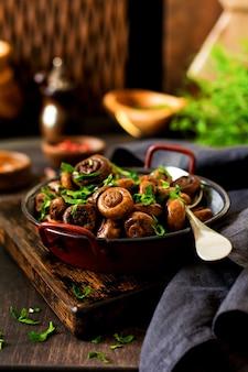 きのこシャンピニオンを醤油で揚げ、コショウと玉ねぎの蒸し物を古いヴィンテージのテーブルの古い金属製のボウルに入れます。セレクティブフォーカス