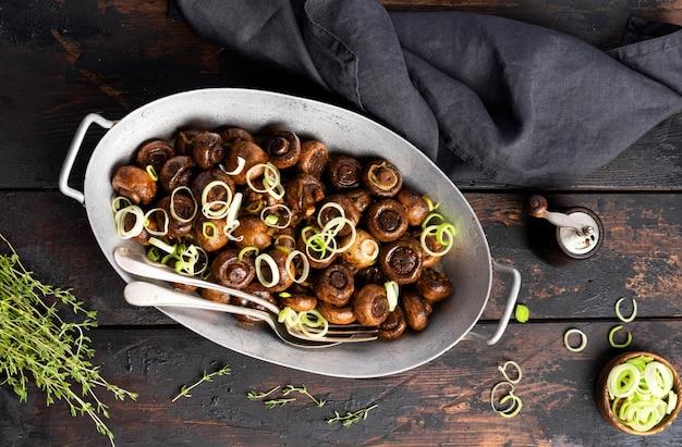 오래 된 빈티지 테이블에 오래 된 금속 그릇에 후추와 찐 양파와 간장에 튀긴 버섯 샴 피뇽. 선택적 초점