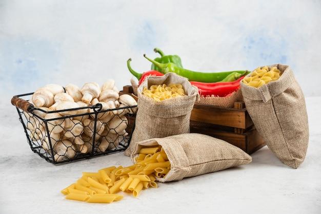 Грибы, перец чили и макаронные изделия в деревенской корзине на белом столе.