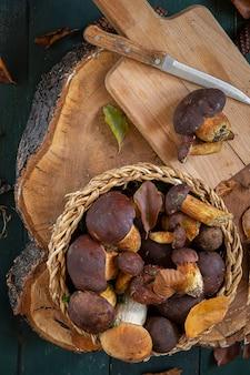 Грибы в корзине на разделочную доску с ножом. сезонный сбор грибов. подготовка к зиме, изготовление самодельных маринадов.