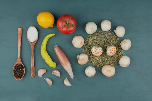 Грибы, лимон, перец, мята, помидоры и специи на синем столе.