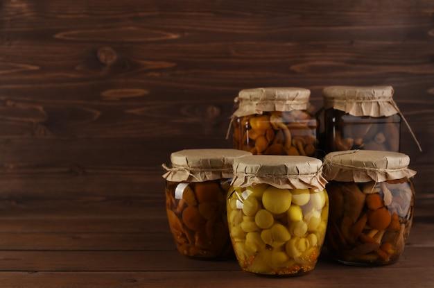 キノコのマリネ木製の背景にガラスの瓶。素朴な発酵きのこはコピースペースで背景を広げます。